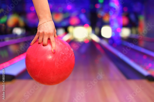 Foto Female hand holding ball before throwing in bowling club