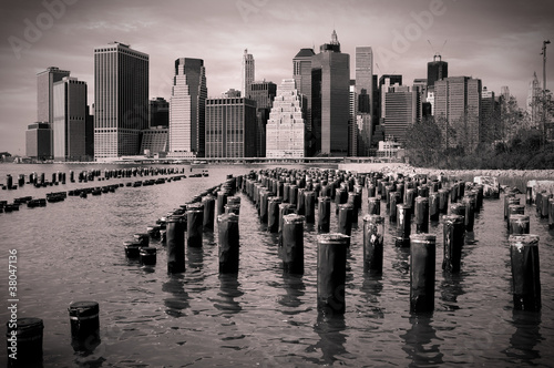 Foto op Plexiglas New York TAXI Skyline von Manhattan mit Holzpfählen im Wasser, schwarzweiss