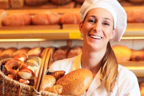 Obraz na plátně Bäckerin verkauft Brot im Korb in Bäckerei
