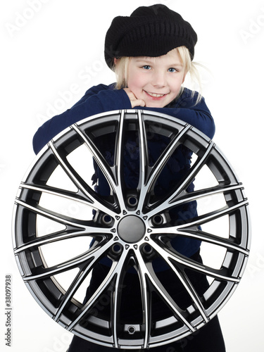 Fotografie, Obraz Cute blonde girl with knit cap leans over an aloy wheel