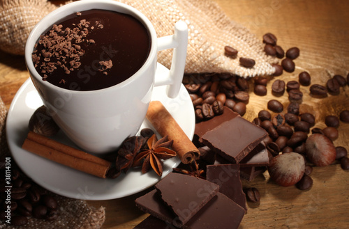 Staande foto Chocolade cup of hot chocolate, cinnamon sticks, nuts and chocolate