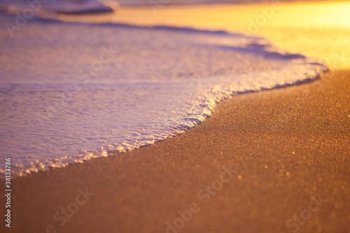 fale-wymywajace-piasek-o-zachodzie-slonca-plytka-glebia-ostrosci