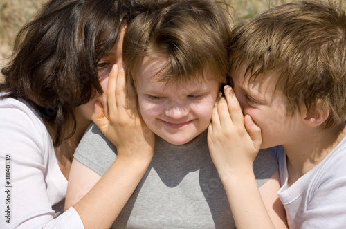 Fotografie, Obraz  Girl and boy whispering secret to their sister.