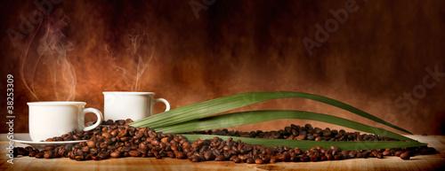 Foto op Plexiglas koffiebar Caffè in tazza, con chicchi sparsi sulla tavola