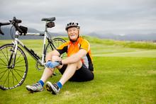 Happy Senior Cyclist Sitting On Grass Resting