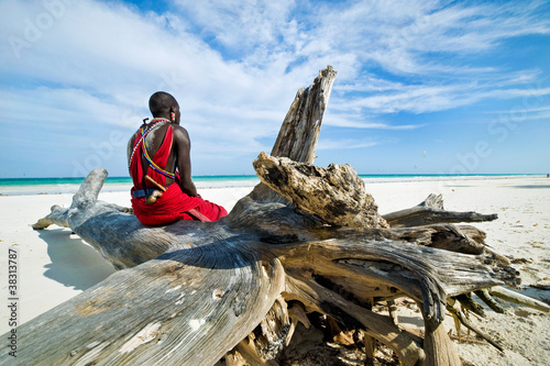 Poster Afrique Maasai sitting by the ocean on the beach