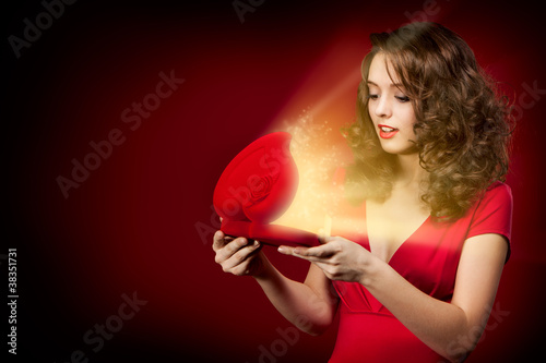 Fotografia, Obraz  Happy girl opening a gift on Valentine's Day