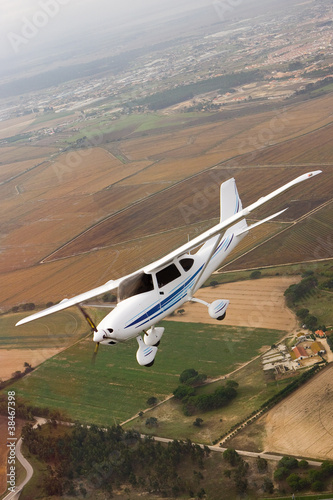 Small airplane flying over farm Fototapeta
