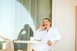Happy female in bathrobe speaking mobile phone on terrace
