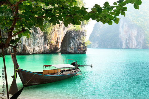 Photo Stands Black long boat on island in Thailand