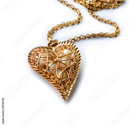 Fotografering Golden pedant in the shape of a heart on the white background