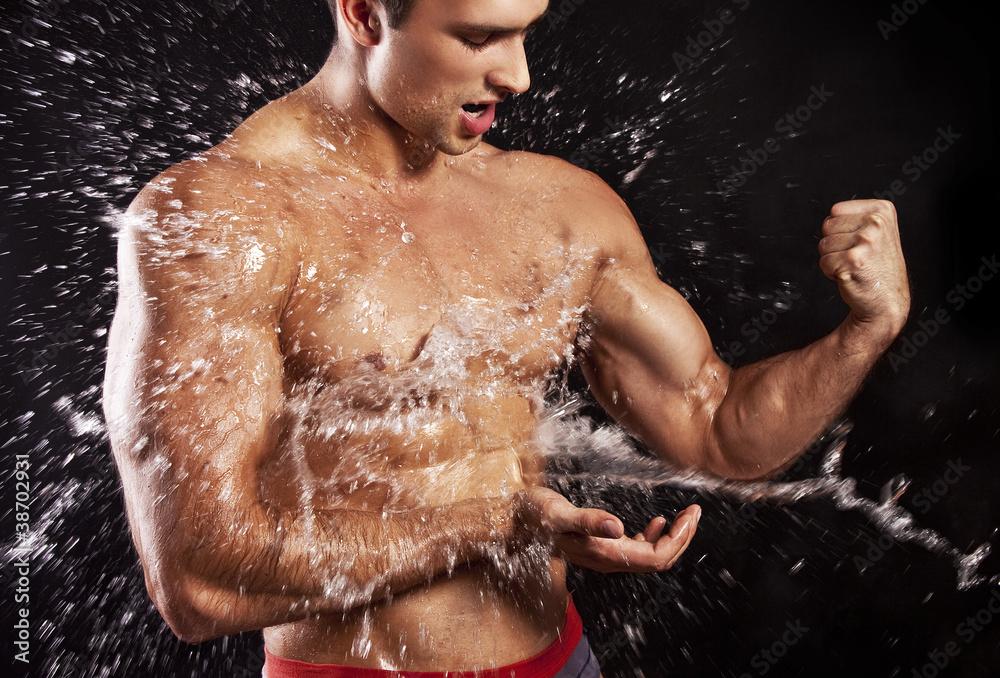 Fototapeta muscular man having shower