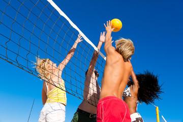 Fototapeta Friends playing beach volleyball