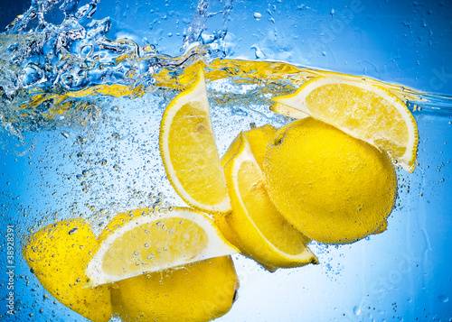 Foto op Canvas Opspattend water Lemon Slices falling deeply under water with a big splash on blu