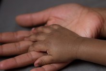 Hand Of A Baby In His Mother's...