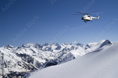 Tuinposter Helicopter Helicopter in snowy mountains