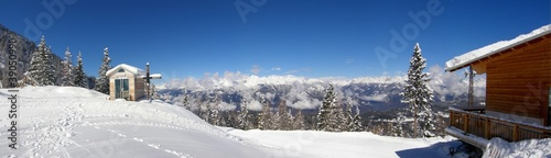 Small snowy chapelle with wooden cross in the mountains panorama Canvas Print
