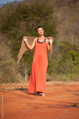 Photo  Beautiful girl dressed  terracotta dress with a scarf in her han
