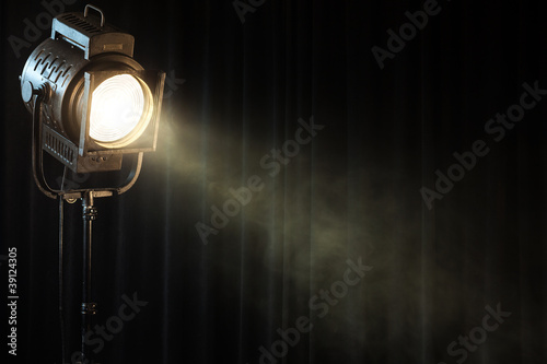 Photo  vintage theatre spot light on black curtain with smoke