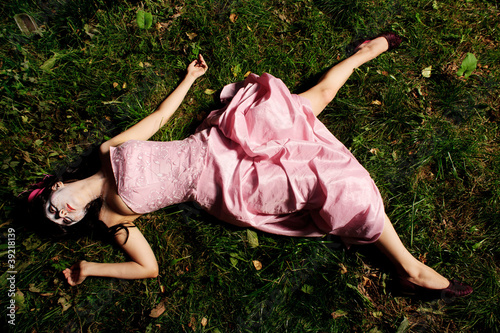 Photo  girl lie on the grass like a corpse