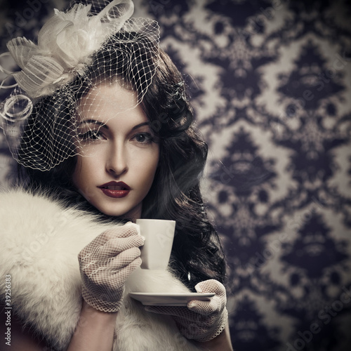 Young beautiful retro lady drinking coffee