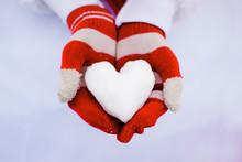 Red Gloves Hold White Snow Heart.