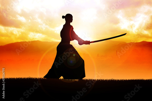 Silhouette of a samurai posing during sunset Poster