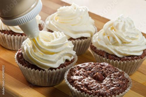 Decorating chocolate muffin with vanilla cream