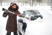 Woman Removing Snow From Car W...