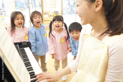 Fotografie, Obraz  幼稚園教諭のピアノに合わせて歌う幼稚園児