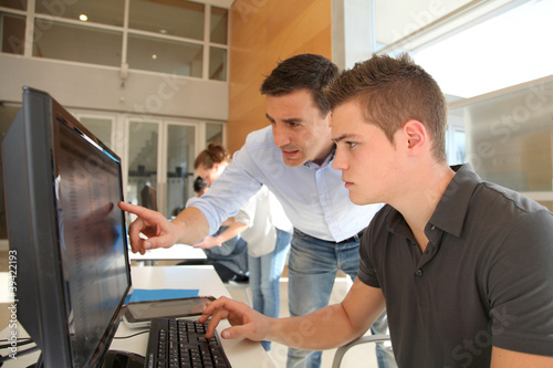 Teacher and student working on computer Wallpaper Mural