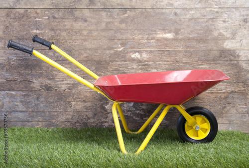 Stampa su Tela wheelbarrow on frass against wooden wall