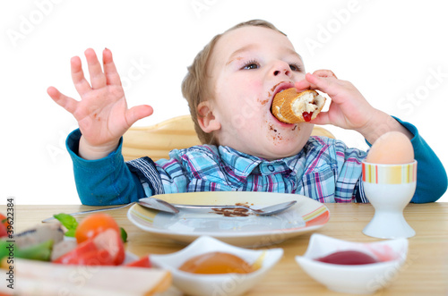 Photographie  kleiner Junge beim Frühstücksbötchen essen