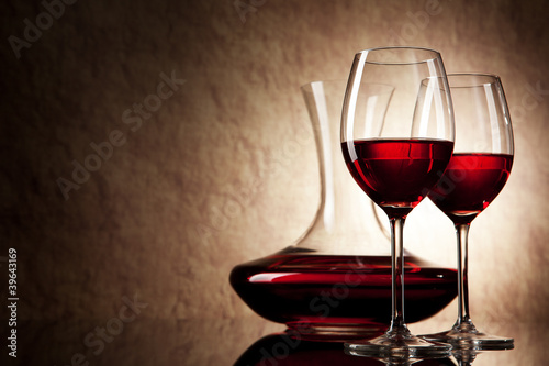 decanter with red wine and glass on a old stone background - 39643169