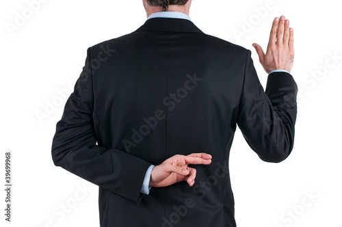 Fotografering  young businessman in suit telling a lie with the fingers crossed