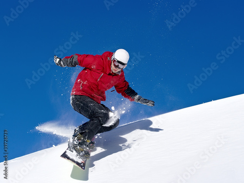 Fotografie, Obraz  Snowboarder jumping through air with deep blue sky