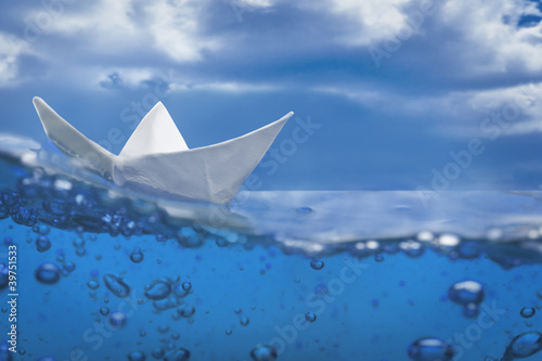 paper ship splash with bubbles sailing in blue water and sky