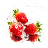 Three fresh strawberries in water splash