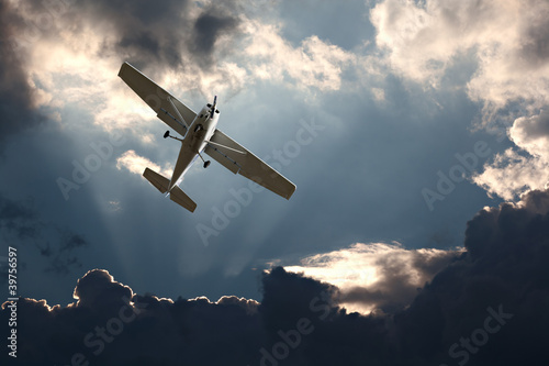 Fotografia Small fixed wing plane against a stormy sky
