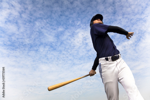 Fotografie, Obraz  baseball player taking a swing with cloud background