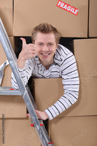 Factory worker emerging from cardboard boxes Canvas Print