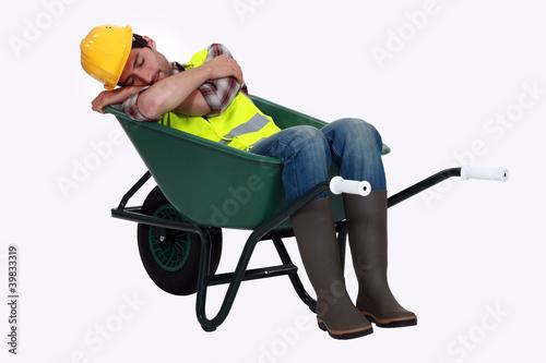 Photo A road worker sleeping in a wheelbarrow.