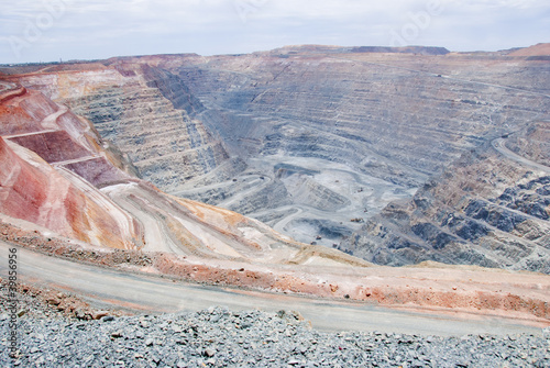Valokuva  Big mine pit with little dump trucks and reddish soil