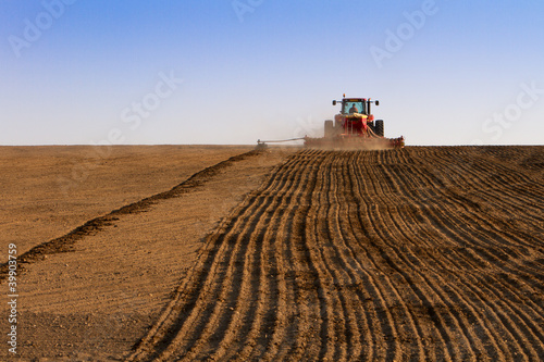 Foto op Canvas Cultuur Agriculture tractor sowing seeds and cultivating field