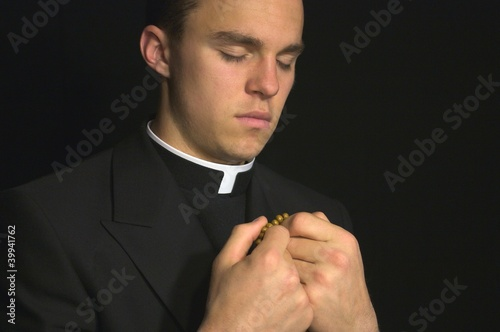 Canvas Print Young Priest praying with rosery in his hands