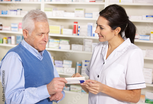 Tuinposter Apotheek American pharmacist serving senior man in pharmacy