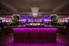 Wooden Bar Counter With Pink Illumination In Large Restaurant