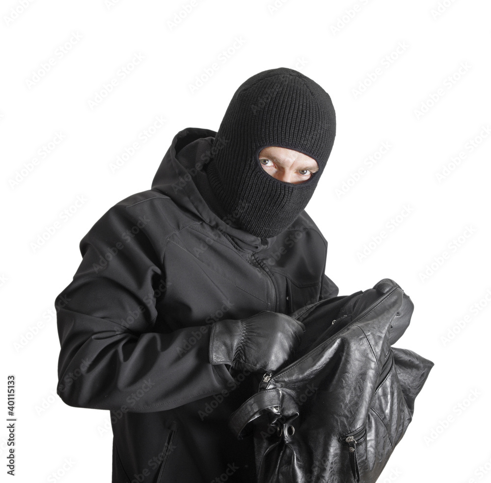 Fototapeta Masked criminal holding a stolen handbag, isolated on white