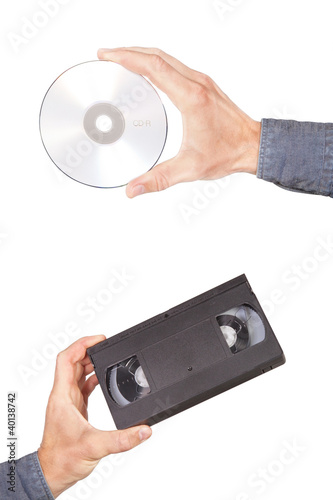 Fotografija  Videotape and cd drive in your hand. On a white background.