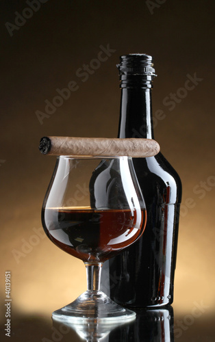 Spoed Foto op Canvas Bar bottle and glass of brandy and cigar on brown background